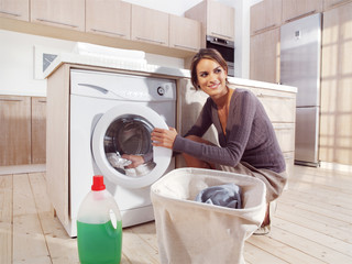 woman putting cloth into washing machine