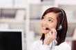 lächelnde junge frau im büro mit headset