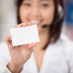 lächelnde service-mitarbeiterin zeigt visitenkarte