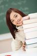 junge studentin schaut hinter bücherstapel hervor