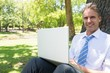 Businessman with laptop leaning on tree trunk