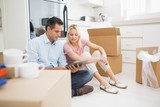 Couple using digital tablet amid boxes in house
