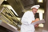 Smiling male cook writing on clipboard in kitchen