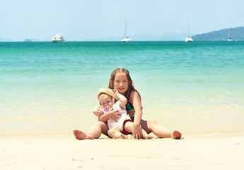 Two happy smiling sisters sitting on a tropical beach.