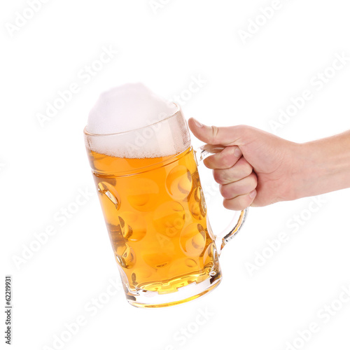 Mug of beer with froth in hand.