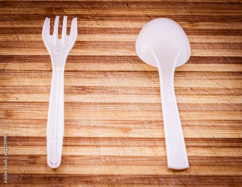 Plastic knife and fork on old wooden surface. Selective focus.