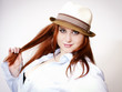 Beautiful young woman with fine red hair wearing hat