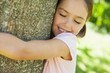 Smiling girl hugging tree with eyes closed at park