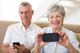 Senior couple sitting on couch using their smartphones