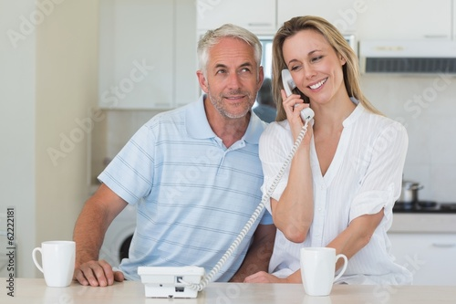 Smiling man listening in on his partners phone call