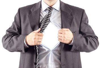 Businessman in superman pose tearing his shirt open to reveal