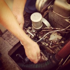 Man fixing old boat engine