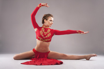 Gorgeous sporty woman in red clothing. Chinese dancing