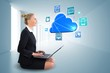 Blonde businesswoman sitting using laptop with cloud and app