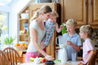 Mother with kids preparing healthy drink with milk and fruits