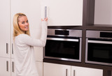 Woman opening the kitchen cabinet and smiling