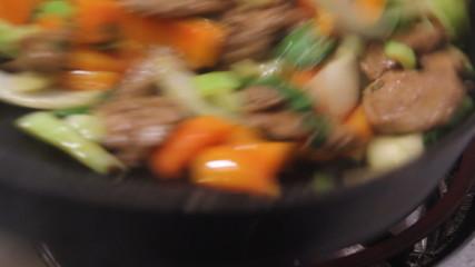 pork stir fry cooking closeup on wok real time