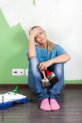 Tired woman  with paint tools