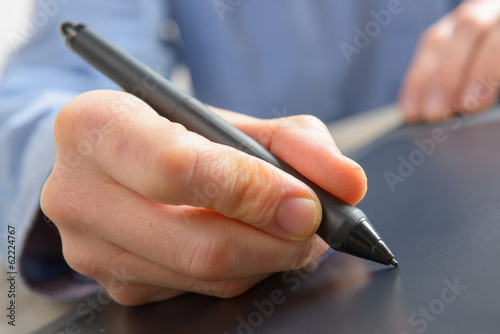 Hands holding graphic tablet pen