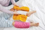 Mutter macht Wadenwickel bei Kind