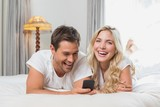 Cheerful relaxed couple reading text message in bed