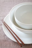 Empty white plate and bowl with chopsticks