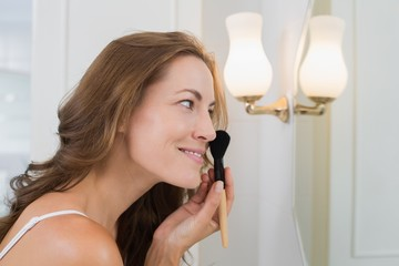 Side view of a beautiful woman applying make-up