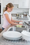 Side view of a girl washing utensils in kitchen