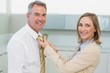 Woman adjusting businessman's tie in kitchen