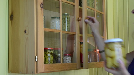 girl from kitchen cupboards inspect jar of canned tomato