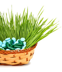 Pills, tablets and wheat grass in the basket