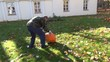 farmer man roll big orange pumpkin through autumn garden meadow