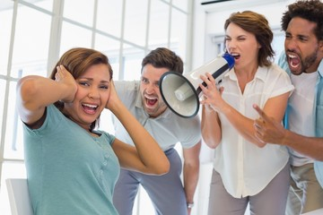 Colleagues yelling through megaphone at businesswoman