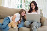 Mother using laptop by daughter on sofa