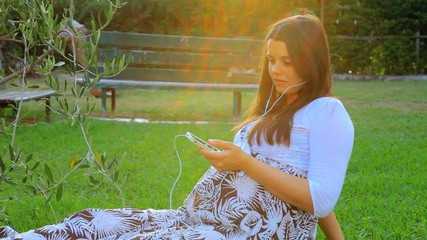 Gorgeous pregnant woman listening music in garden