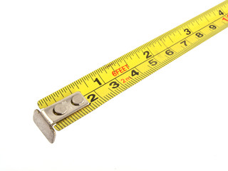Close up photo of a yellow tape measure on a white background.