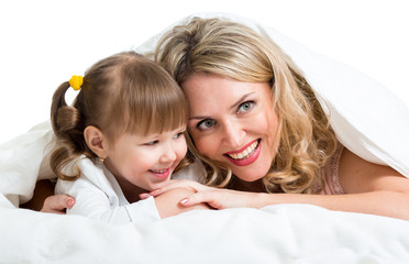 happy mother and child lie in the bed