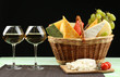 Basket with different cheese and glasses of wine