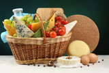 Basket with tasty dairy products on dark background