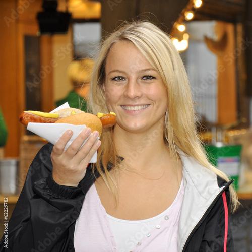 Frau isst Rostbratwurst von Imbiss