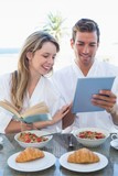 Couple with book and digital tablet on breakfast table