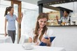 Smiling woman using digital tablet in coffee shop