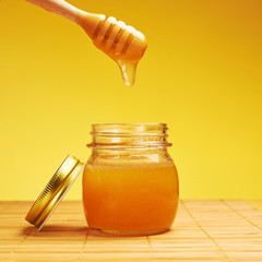 Honey jar with wooden dipper composition