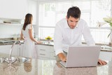 Man using laptop with woman in background at kitchen