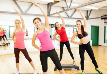group of smiling female stretching in gym
