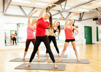 group of smiling women stretching in the gym