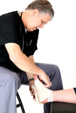 Mature podiatrist in scrubs wrapping a girl' ankle