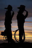 Silhouette of two young cowboys standing with a sunset backgroun