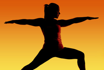 Silhouette of fit yoga model with orange and yellow background