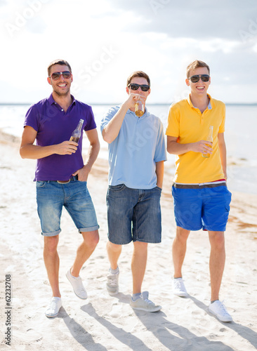 male friends on the beach with bottles of drink